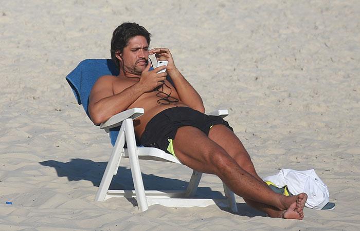 Léo, da dupla com Victor, toma sol, enquanto escuta música na Barra da Tijuca