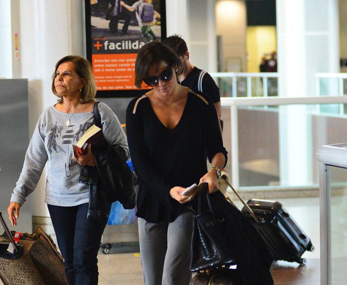 Presa no celular, Deborah Secco deixa o Rio de Janeiro