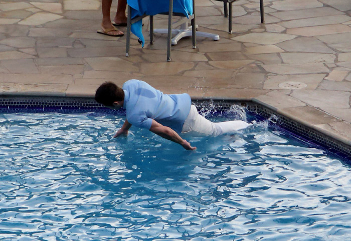 Zac Efron cai na piscina de roupa em filmagem no Havaí