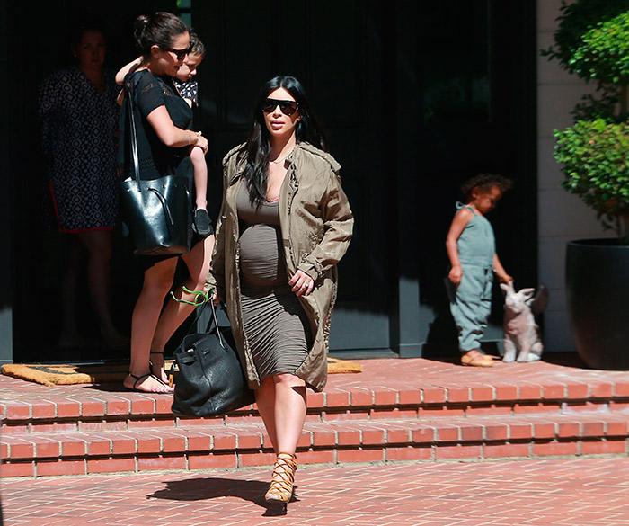 Kim Kardashian exibe barrigão ao levar filha para uma festa