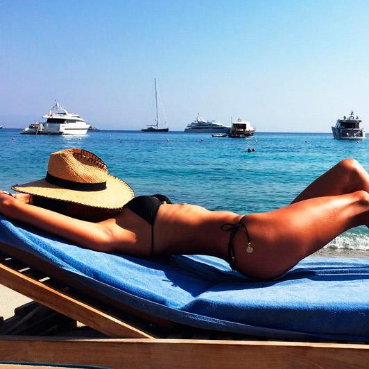 Alessandra Ambrósio cobre o rosto com chapéu e mostra corpão