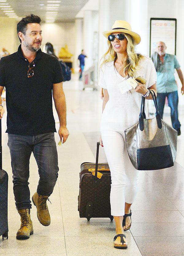 Adriane Galisteu embarca com o maridão em aeroporto
