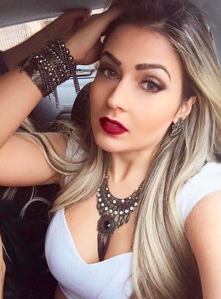 Camila Braga aposta no batom vermelho e nos acessórios em selfie