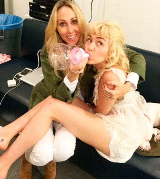 Miley Cyrus posa tomando mamadeira no colo da mãe