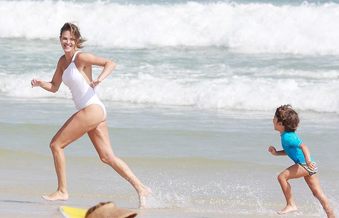 De maiô branco,  Letícia Birkheuer brinca com filho na praia