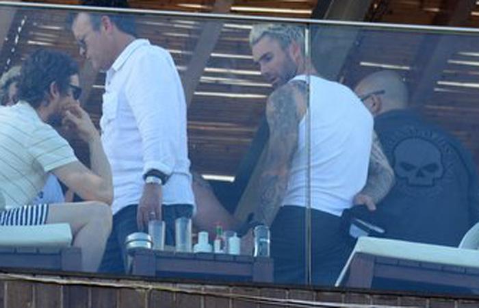 Adam Levine acena para fãs da cobertura do hotel