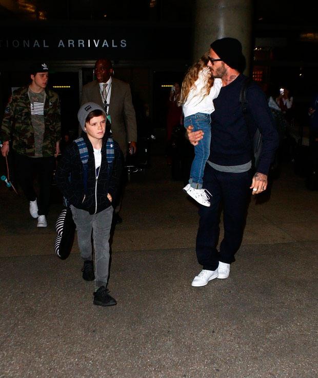 Papai! David Beckham chega em Los Angeles com Harper no colo