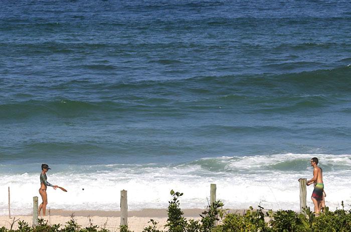 Com o namorado, Fernanda de Freitas se exercita em praia