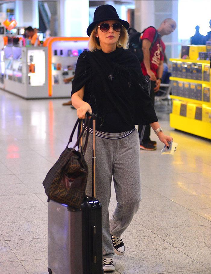 Estilosa, Deborah Secco acena para fotógrafo antes de viagem