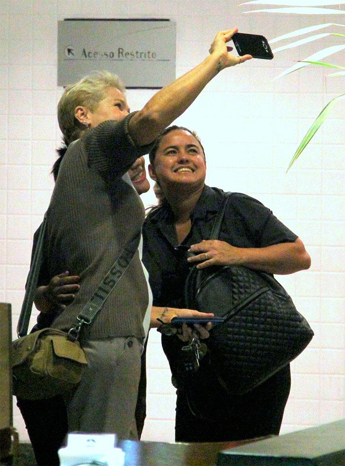 Xuxa tira fotos com fãs durante compras no shopping