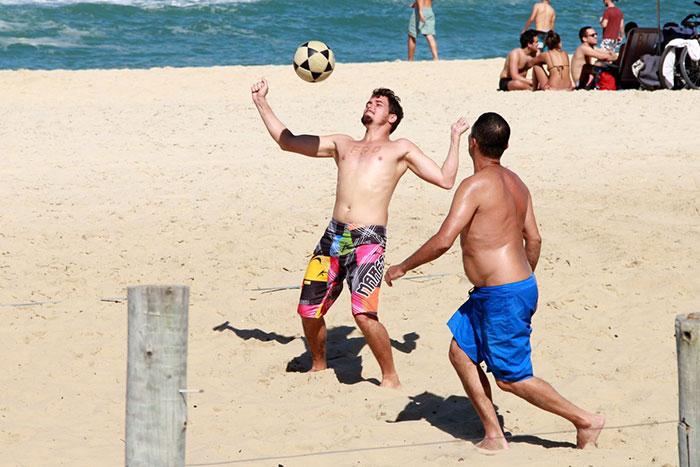 Sem camisa, Felipe Dylon se diverte com amigos na praia
