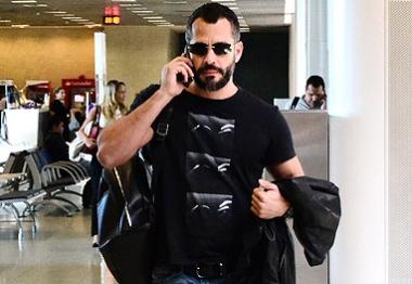 Grudado no celular, Malvino Salvador deixa o Rio de Janeiro