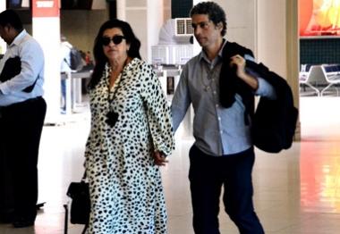 Regina Casé viaja de mãos dadas ao marido