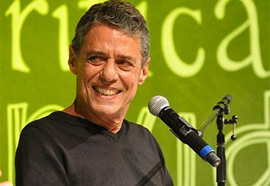 Chico Buarque sorridente em frente ao microfone