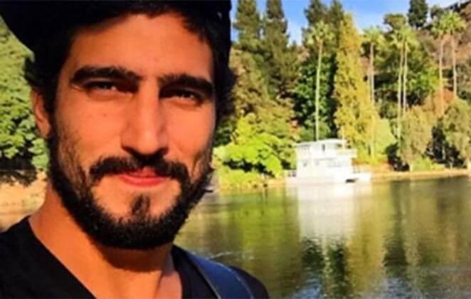 Renato Góes em close, em frente a um lago