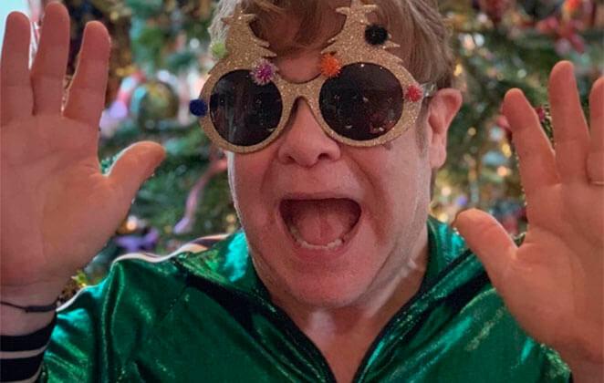 Elton John com óculos extravagante e roupa verde