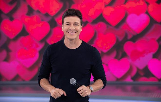 Rodrigo Faro de blusa preta, segurando o microfone, no palco de atração da Record