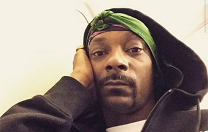 Close de Snoop Dogg, de lenço e touca, segurando o rosto