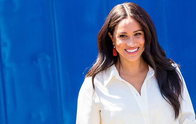 Meghan Markle de camisa branca, sorridente, com fundo azul