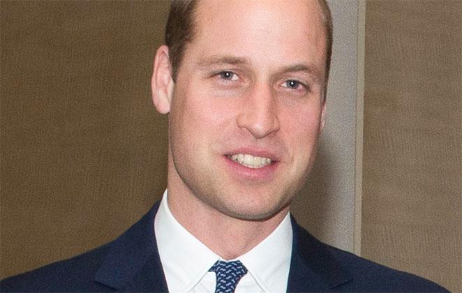 Príncipe William de terno e gravata, posa para fotógrafo