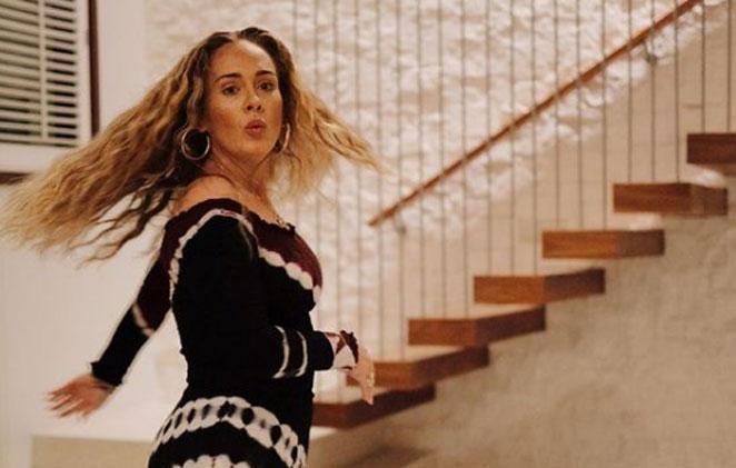 Adele em foto com os cabelos soltos e rodando o vestido