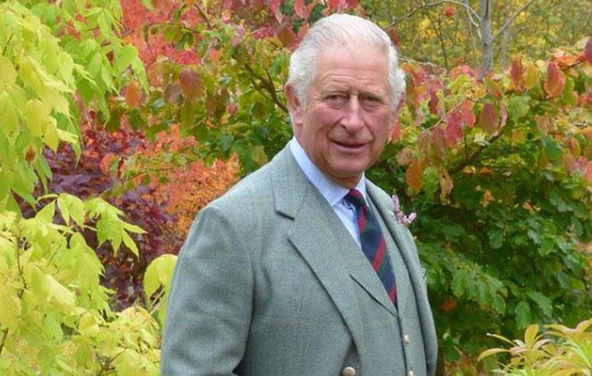 Príncipe Charles de terno e gravata em um jardim