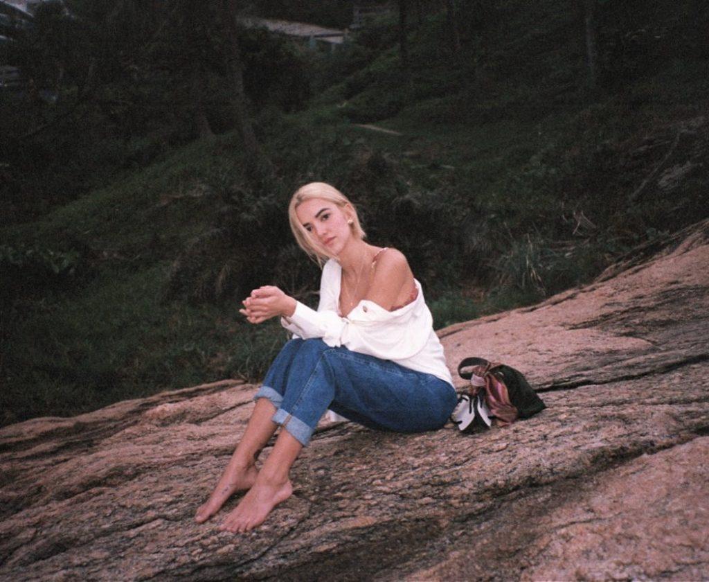 Manu Gavassi sentada numa pedra na praia