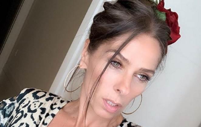 Adriane Galisteu com uma rosa vermelha nos cabelos