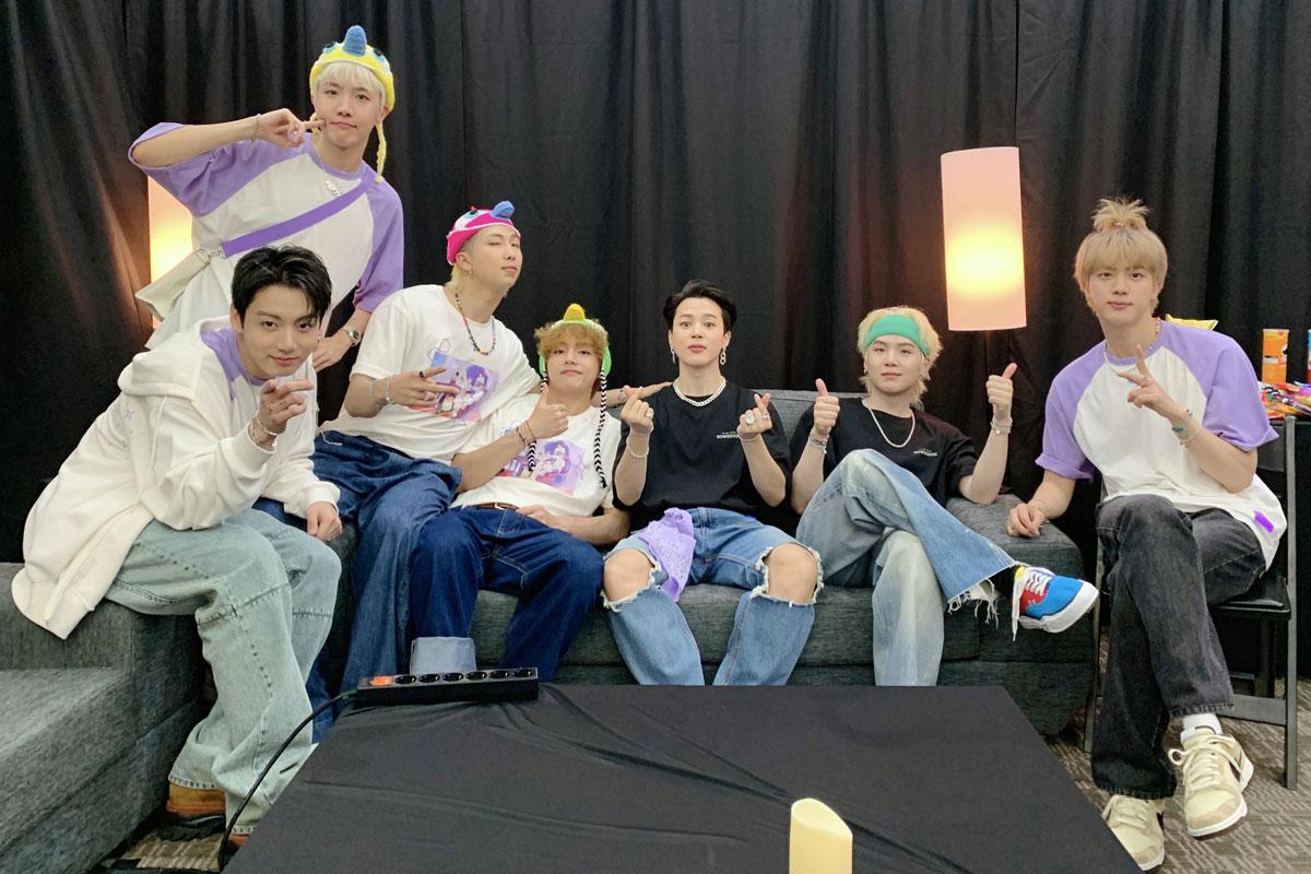 Meninos do BTS, sentados lado lado, em sofá, nos bastidores de show