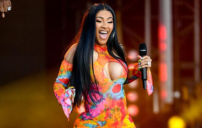 Cardi B sorridente, segurando microfone e com roupa colorida