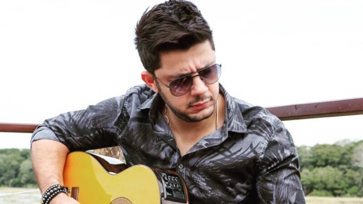 cristiano araujo tocando violão de forma centrada e usando óculos escuros
