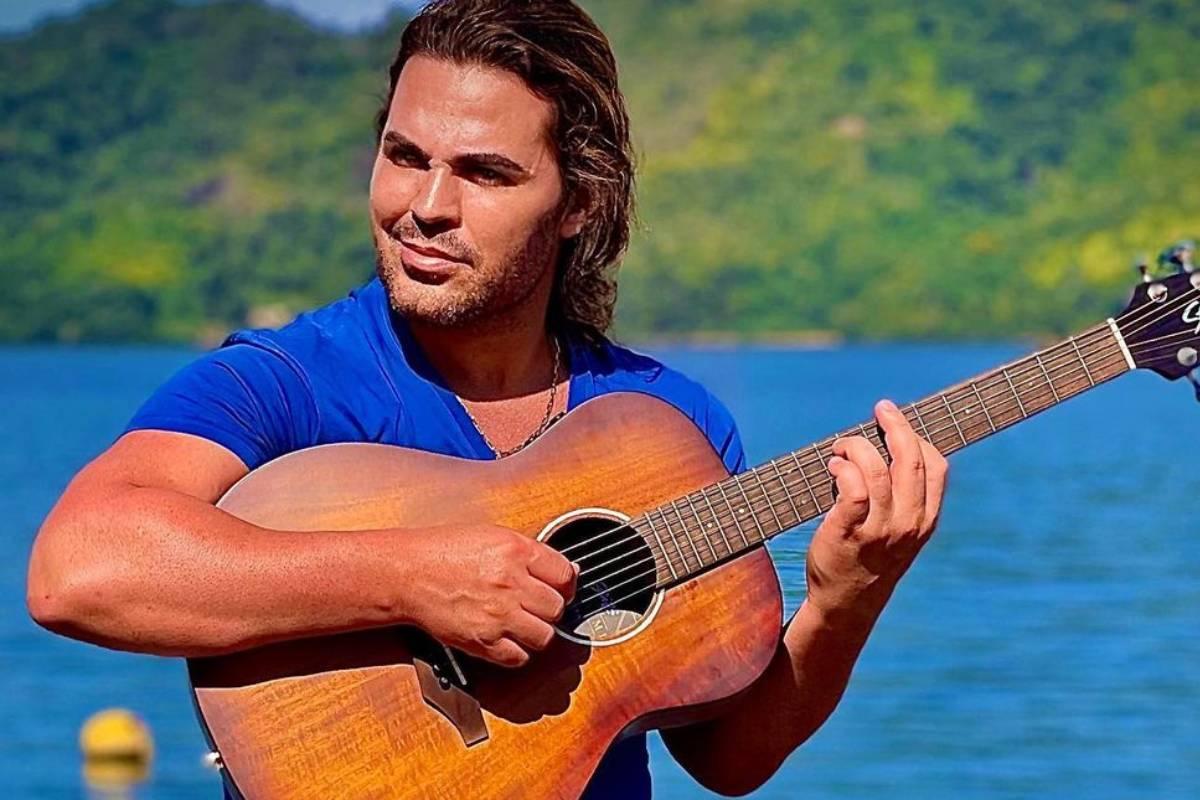 eduardo costa tocando violão em cenário com água e natureza