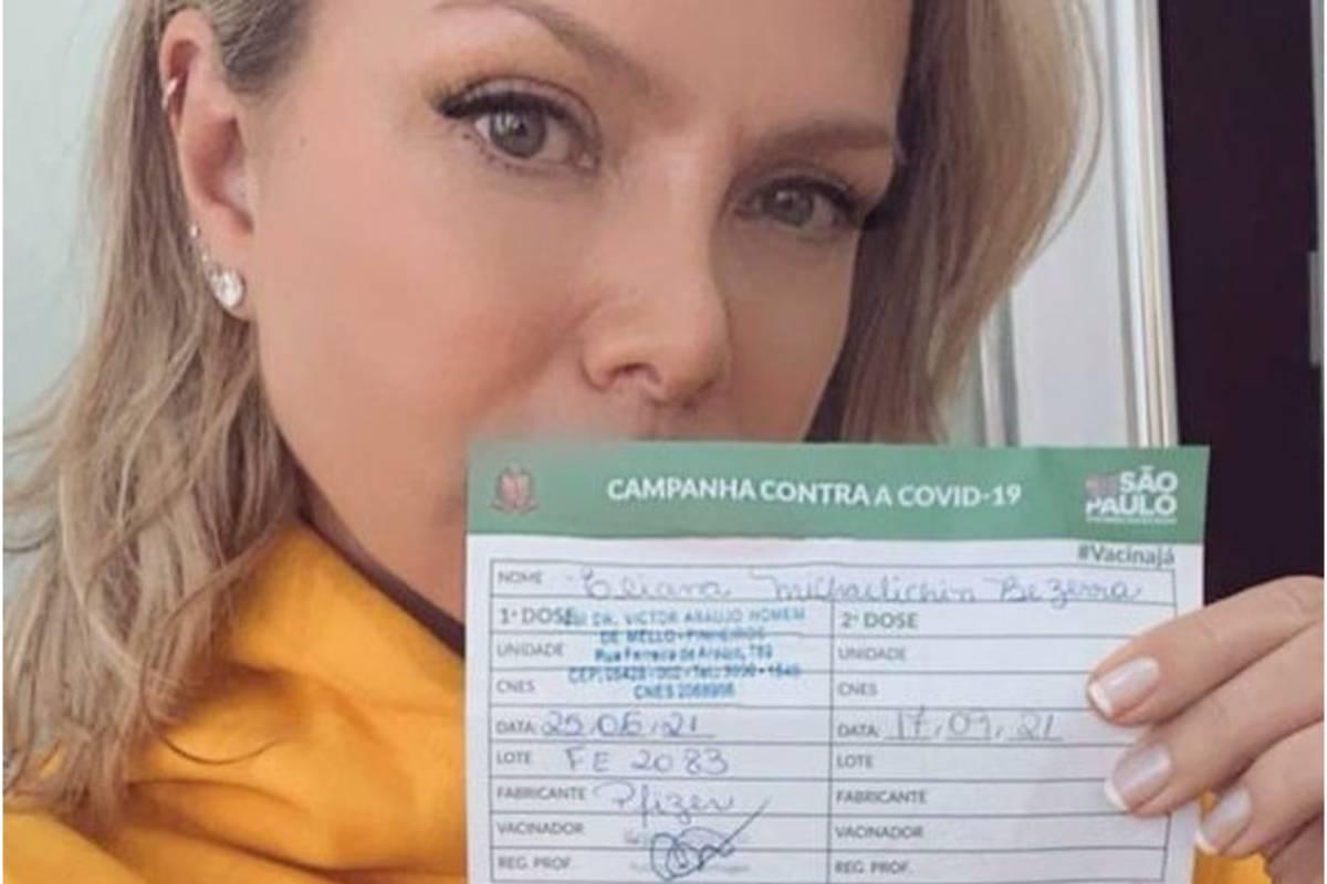 eliana mostrando carteirinha de vacinação após receber primeira dose de vacina contra covid-19