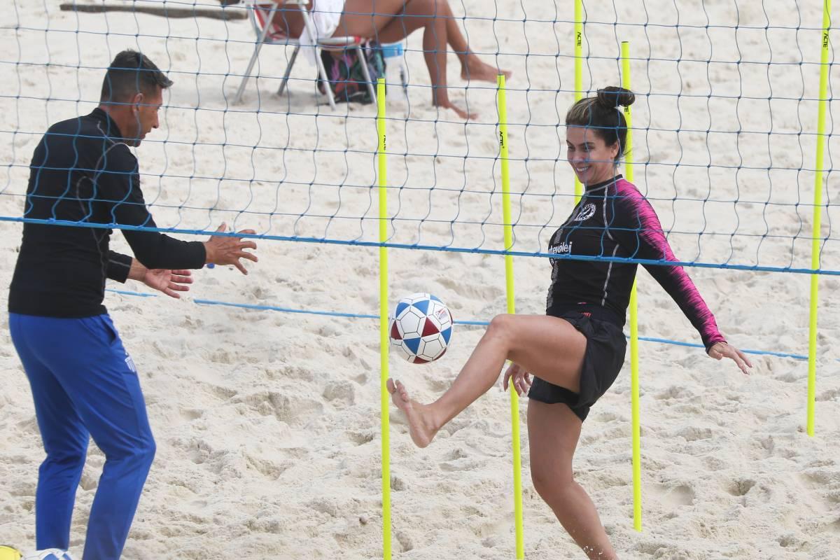giovanna antonelli pratica futevôlei com personal trainer na praia, chutando uma bola próxima da rede