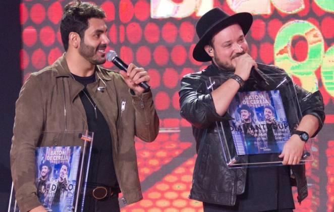 israel e rodolffo em palco com microfones em mãos e segurando placa sobre batom de cereja