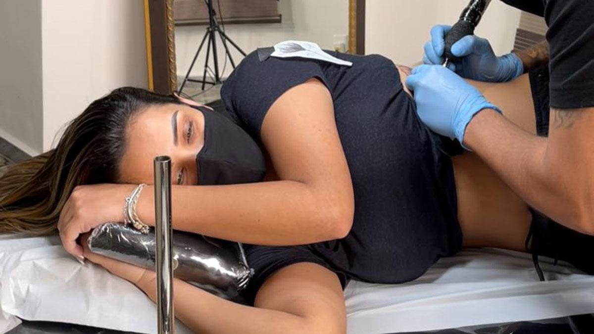 Ivy Moraes deitada na maca enquanto o tatuador faz a tatuagem