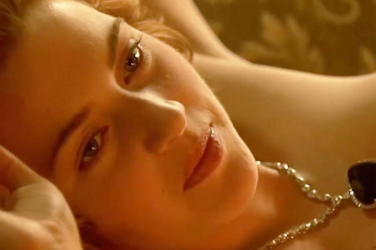 Kate Winslet deitada usando apenas um colar de pérolas