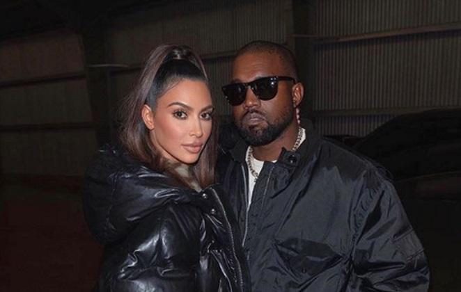 Kin Kardashian e Kanye West de jaqueta preta