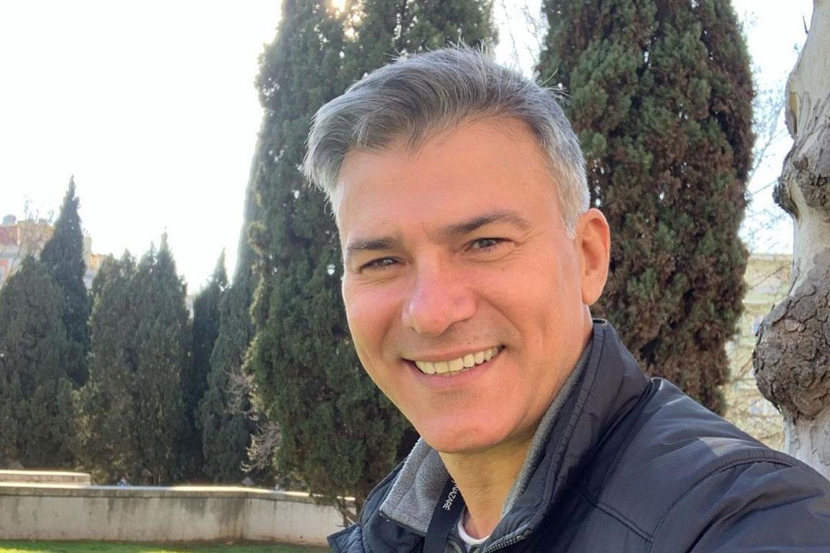 Foto de Leonardo Vieira sem barba e com um fundo repleto de árvores