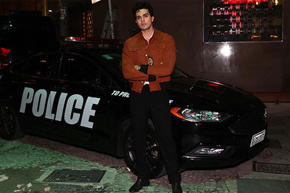 Luan Santana encosta no carro de polícia em clipe