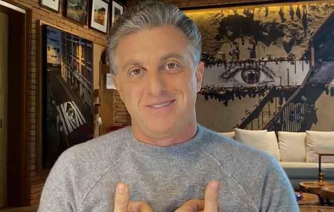 Luciano Huck sorridente de blusão cinza