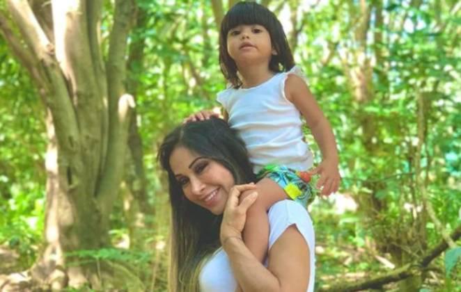 mayra cardi sorri em meio à árvores com a filha sophia nos ombros