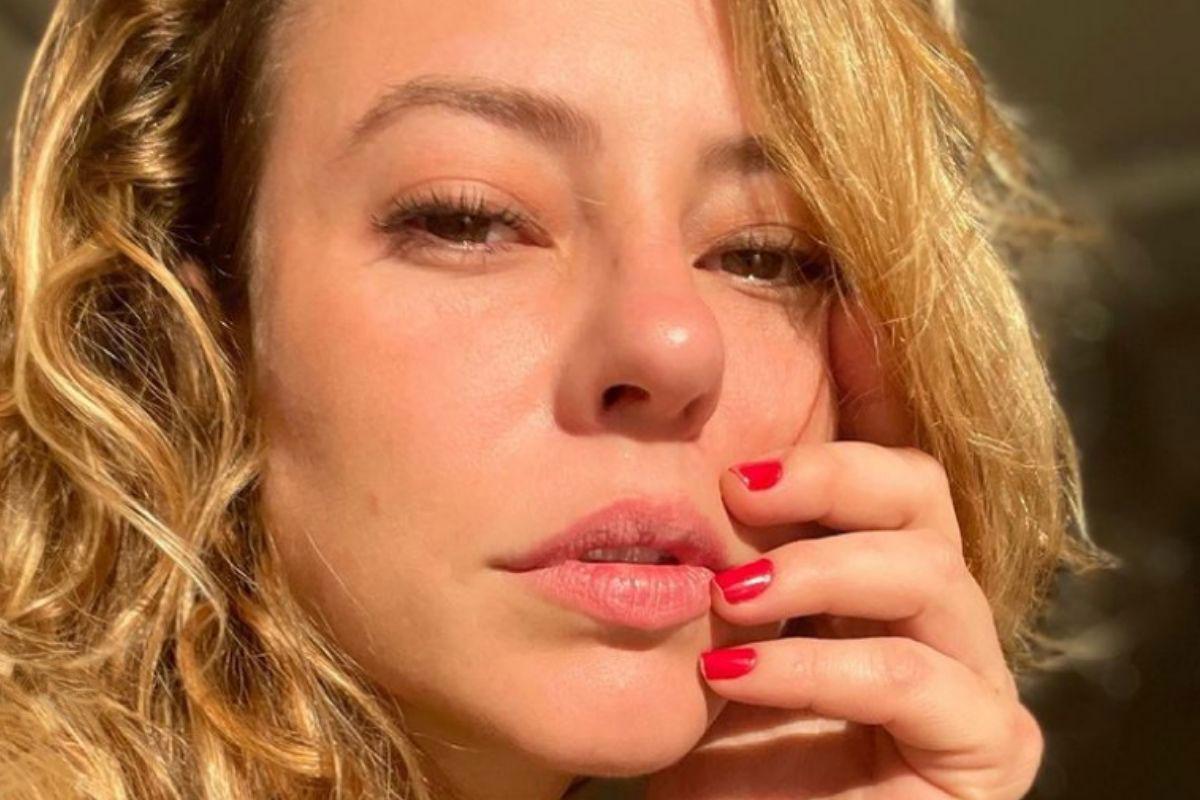 Selfie de Paolla Oliveira iluminada pelo sol com uma das mão apoiadas no rosto