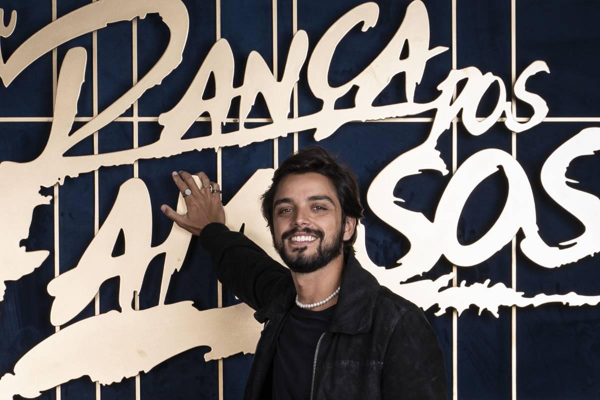 rodrigo simas em frente ao logo do super dança dos famosos