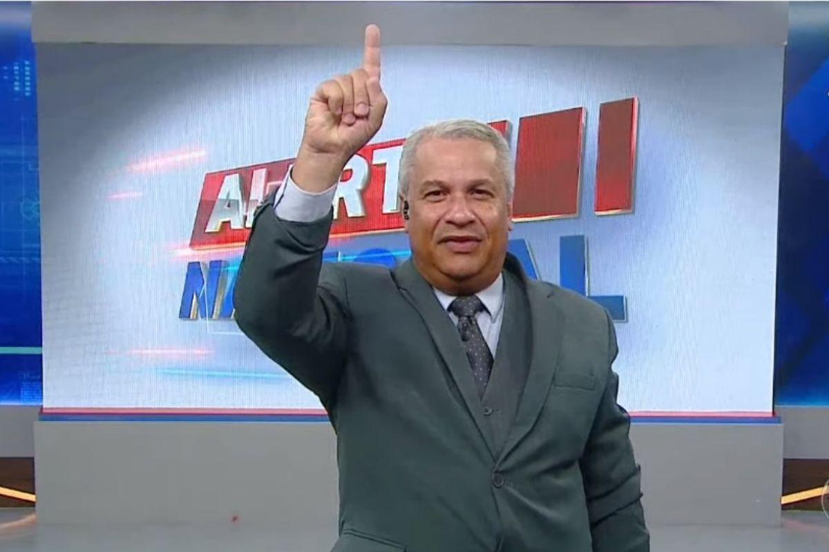 Sikêra Jr. com a mão levantada e dedo indicador apontado para o alto enquanto sorri e apresenta o Alerta Nacional