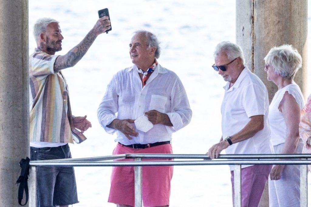 David Beckham conversando animado no Lo Scoglio com a mãe e o pai de sua esposa Victoria, Jackie e Tony