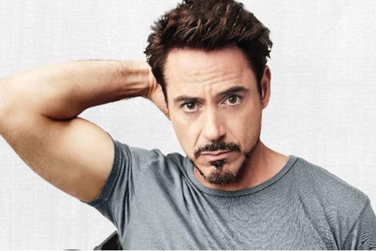 Robert Downey Jr com a mao na cabeca