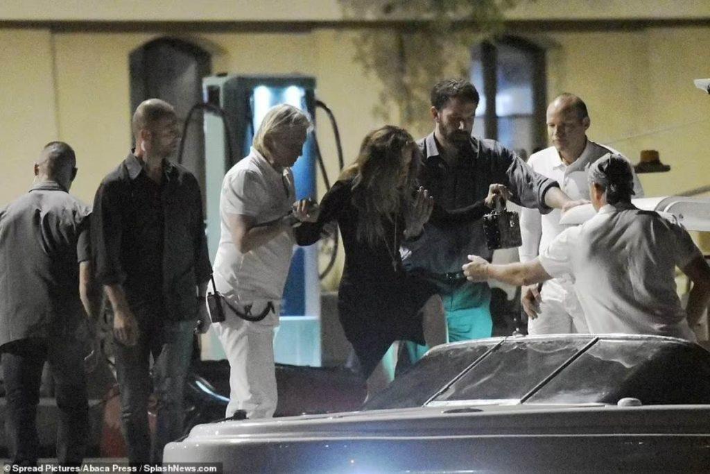 Tripulantes ajudam Jennifer Lopez embarcar em um pequeno barco para retornar ao iate após jantar em Saint-Tropez.
