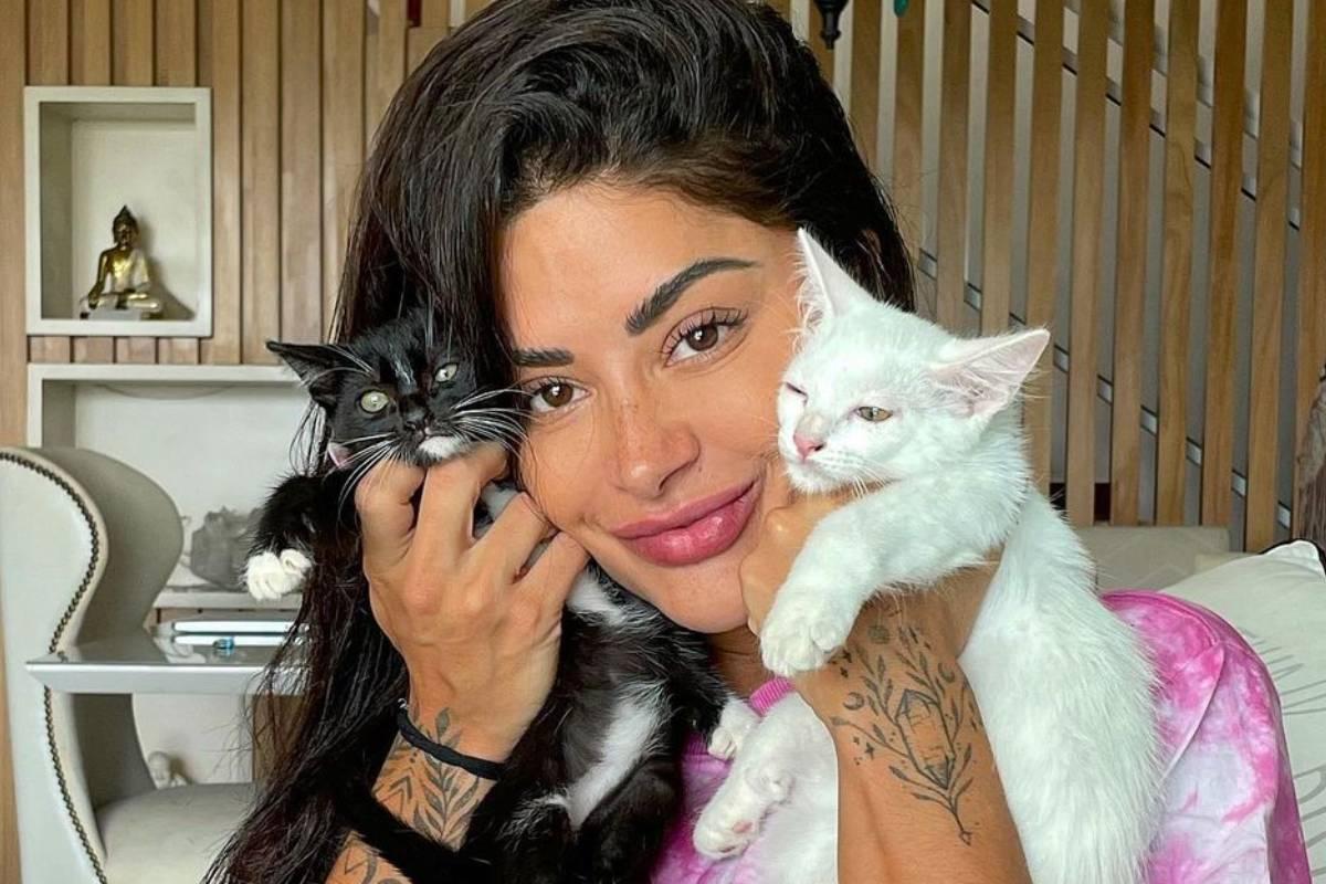 aline riscado posando com um gato preto e um gato branco colados ao rosto