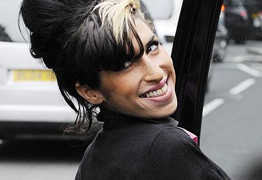 Amy Whinehouse olhando de lado e sorrindo, com a língua nos dentes